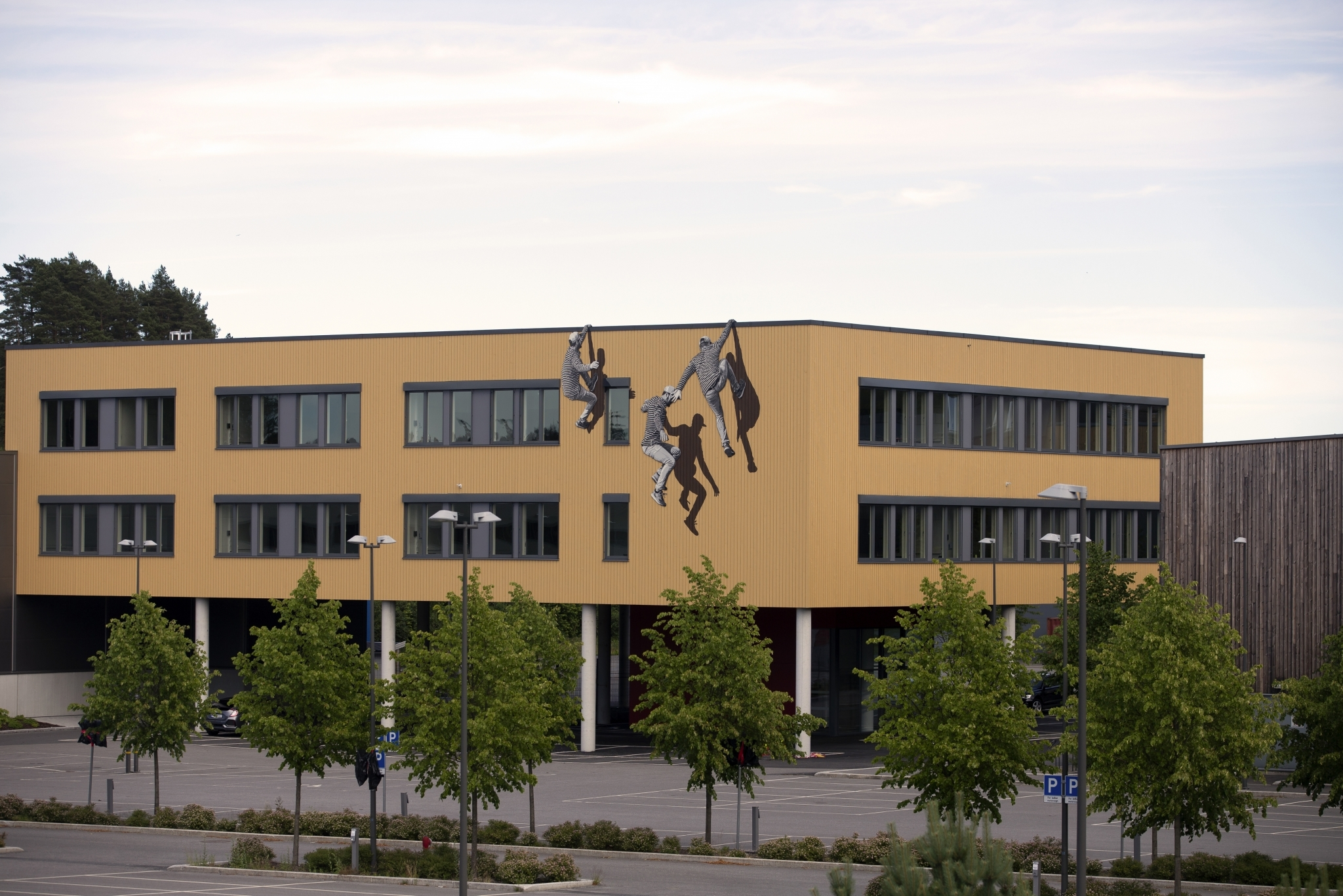 The artist uses shadows with his figures to play with depth whether on eroding buildings or adorning newly constructed offices in norway germany